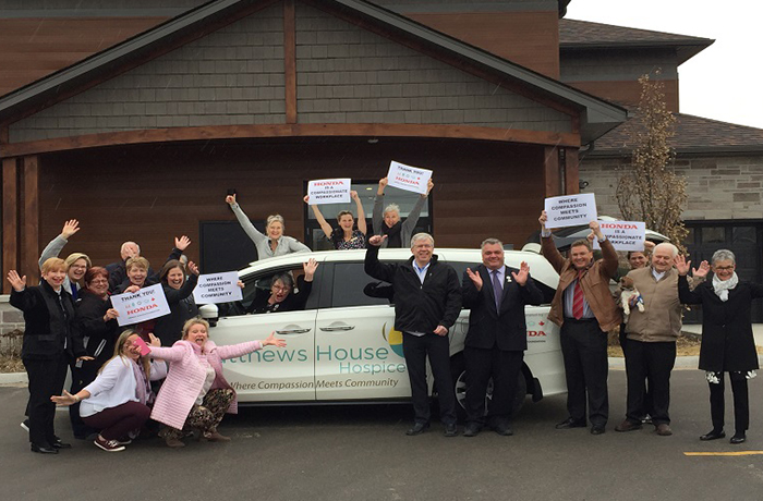 A group of Matthews House Hospice volunteers pose by a brand new Honda Odyssey